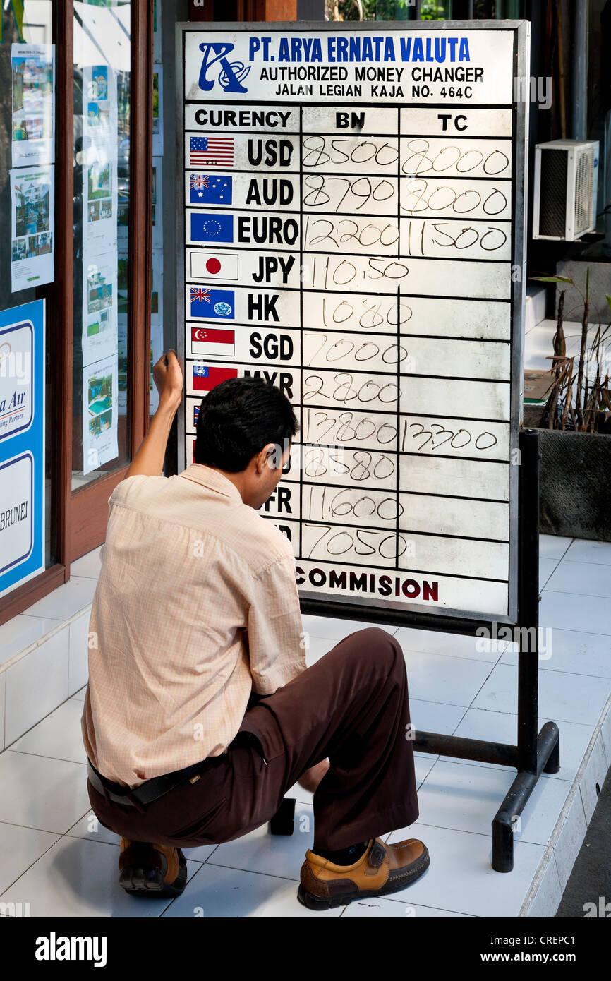 Hombre leyendo los tipos de cambio en un tablero, Kuta, al sur de Bali, Bali, Indonesia, Sudeste Asiático, Asia Foto de stock
