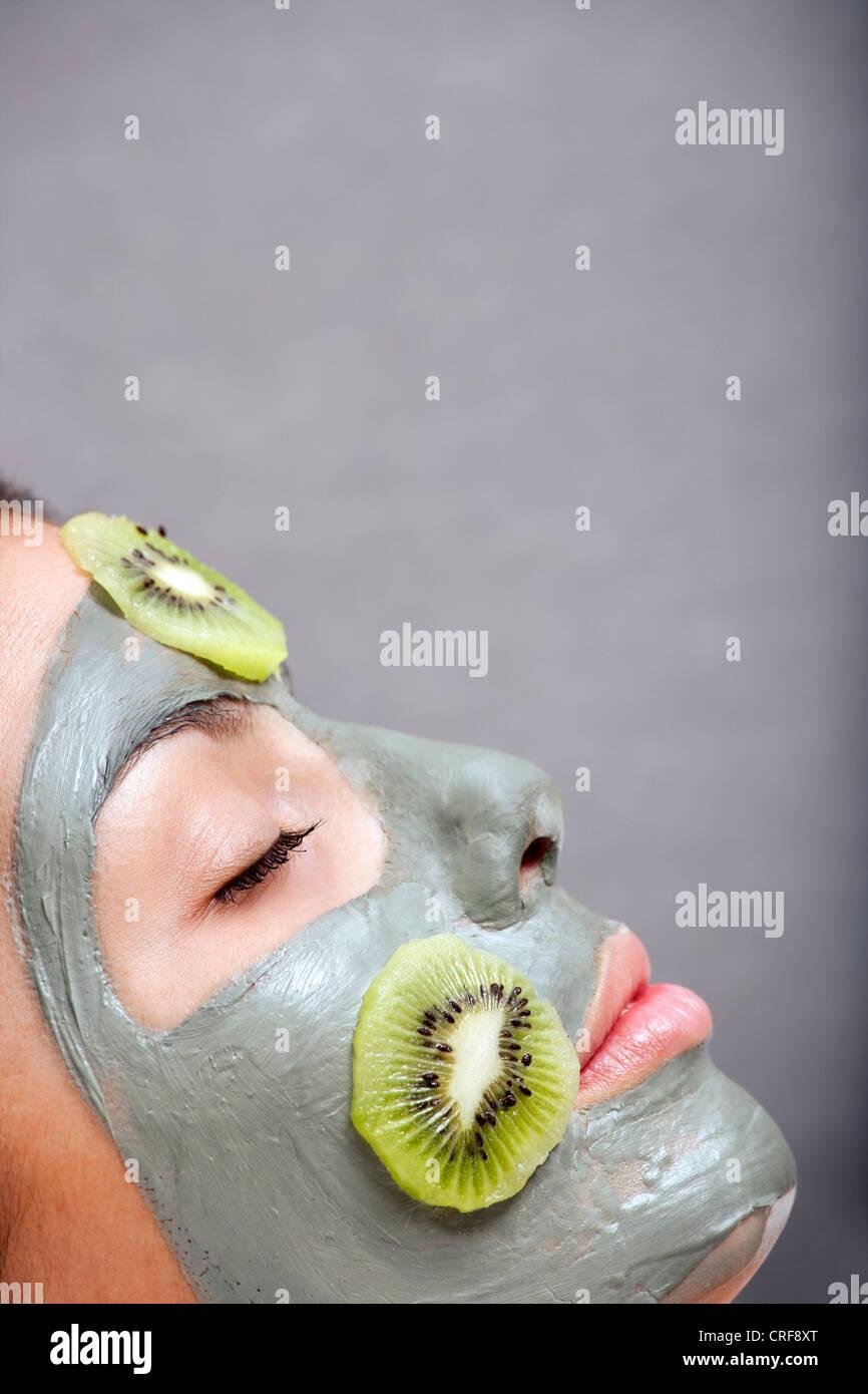 Mujer con máscara de piel y kiwi en Bath Foto de stock