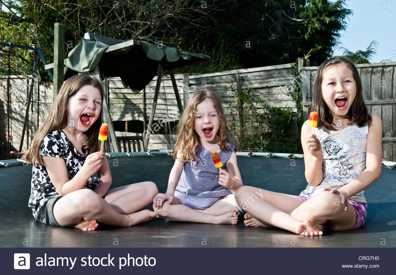 Las niñas comiendo paletas en trampolín Imagen De Stock