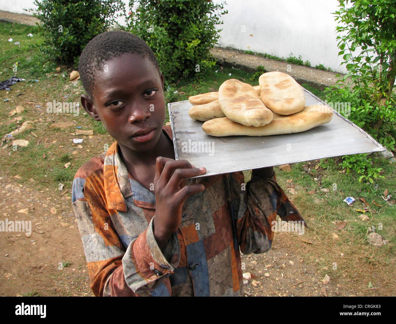 Un muchacho joven con una camisa sucia presenta frish pan en una tableta, Haití, Grande Anse, Dame Marie Imagen De Stock