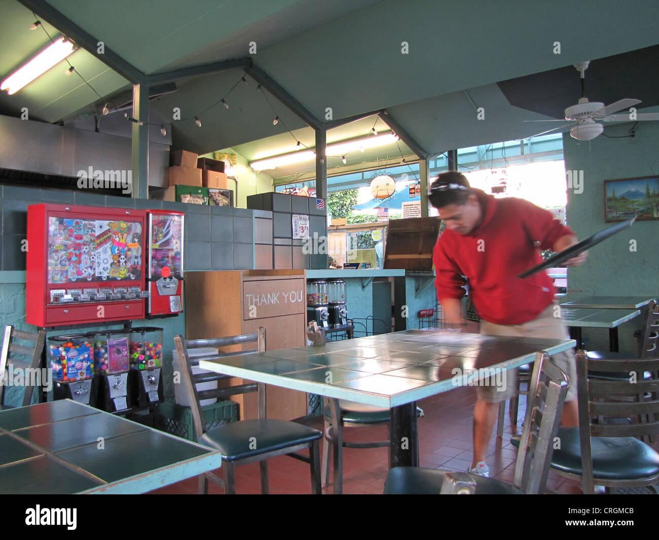 Hombre tabla de limpieza en restaurante de comida rápida americana, goma de mascar de la máquina en la Imagen De Stock