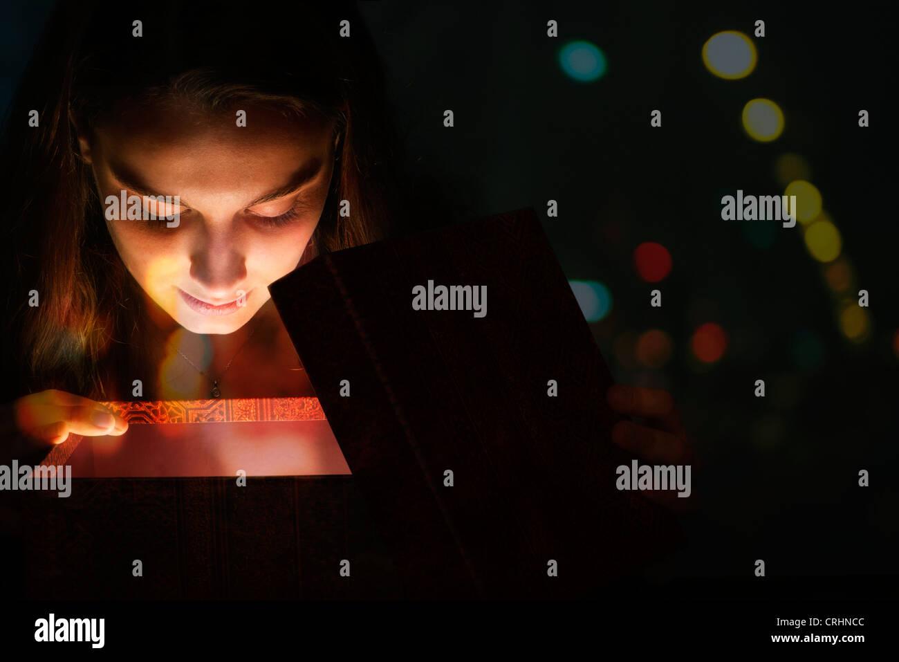 Mujer joven iluminado por la luz de dentro de la caja de regalo Imagen De Stock