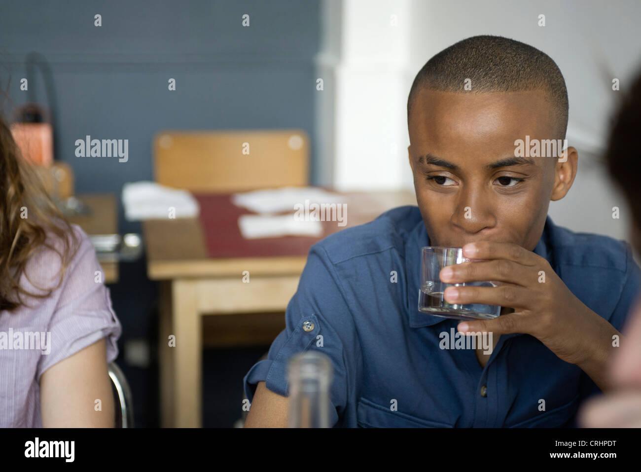 Joven tomando una bebida en la cafetería Imagen De Stock