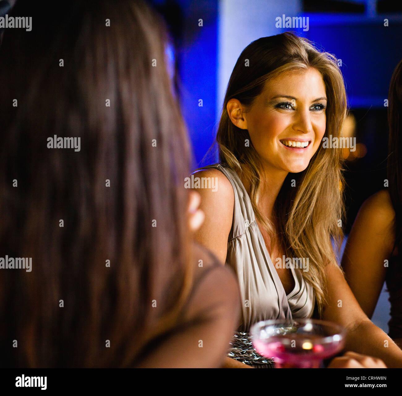 Las mujeres tener bebidas junto al bar Foto de stock