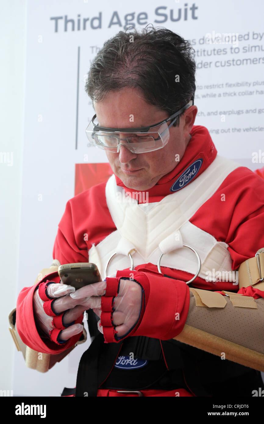 Hombre vestido con un traje de envejecimiento intenta operar un teléfono Blackberry. Imagen De Stock