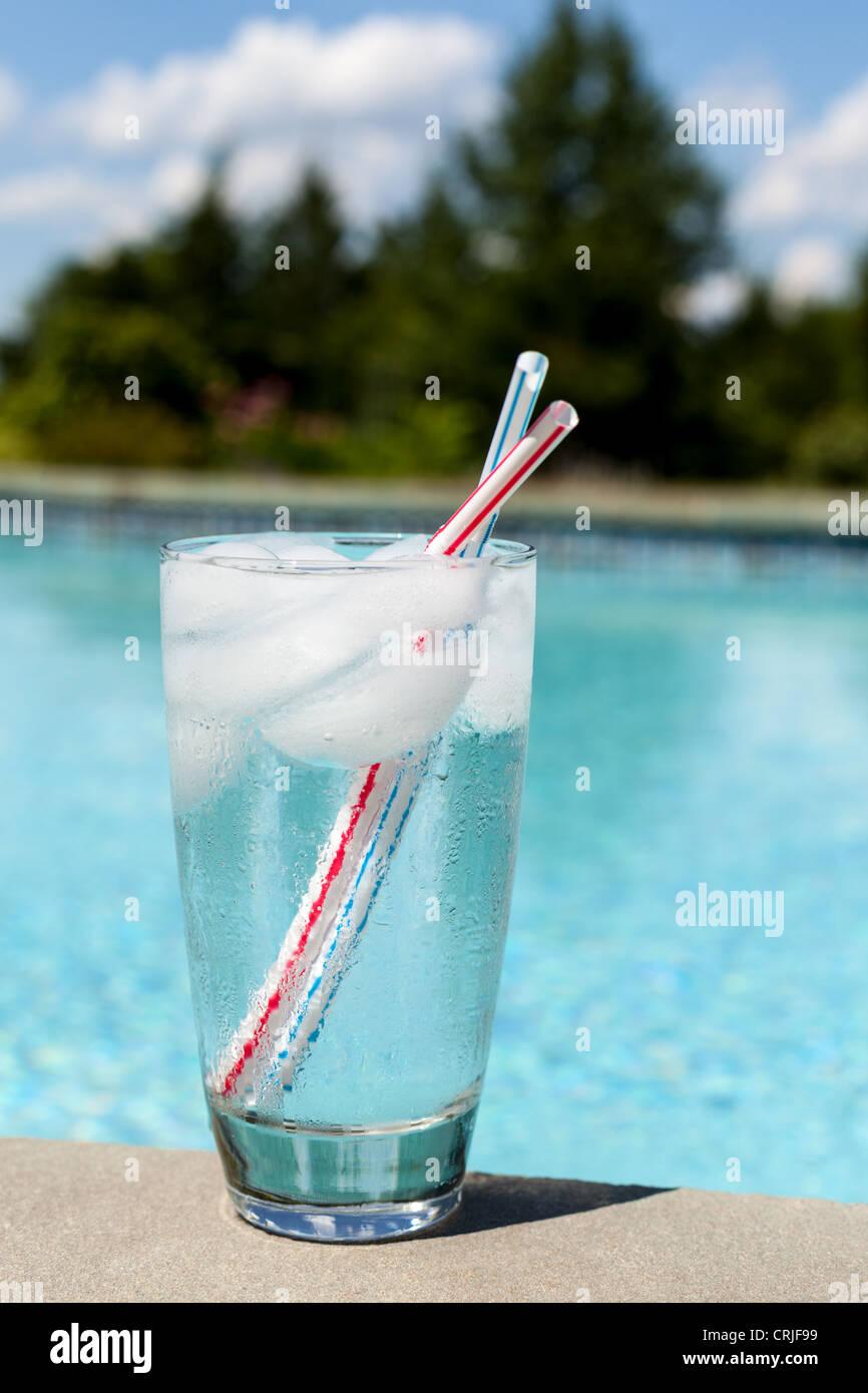 Vaso de agua con cubitos de hielo al lado de la piscina Imagen De Stock