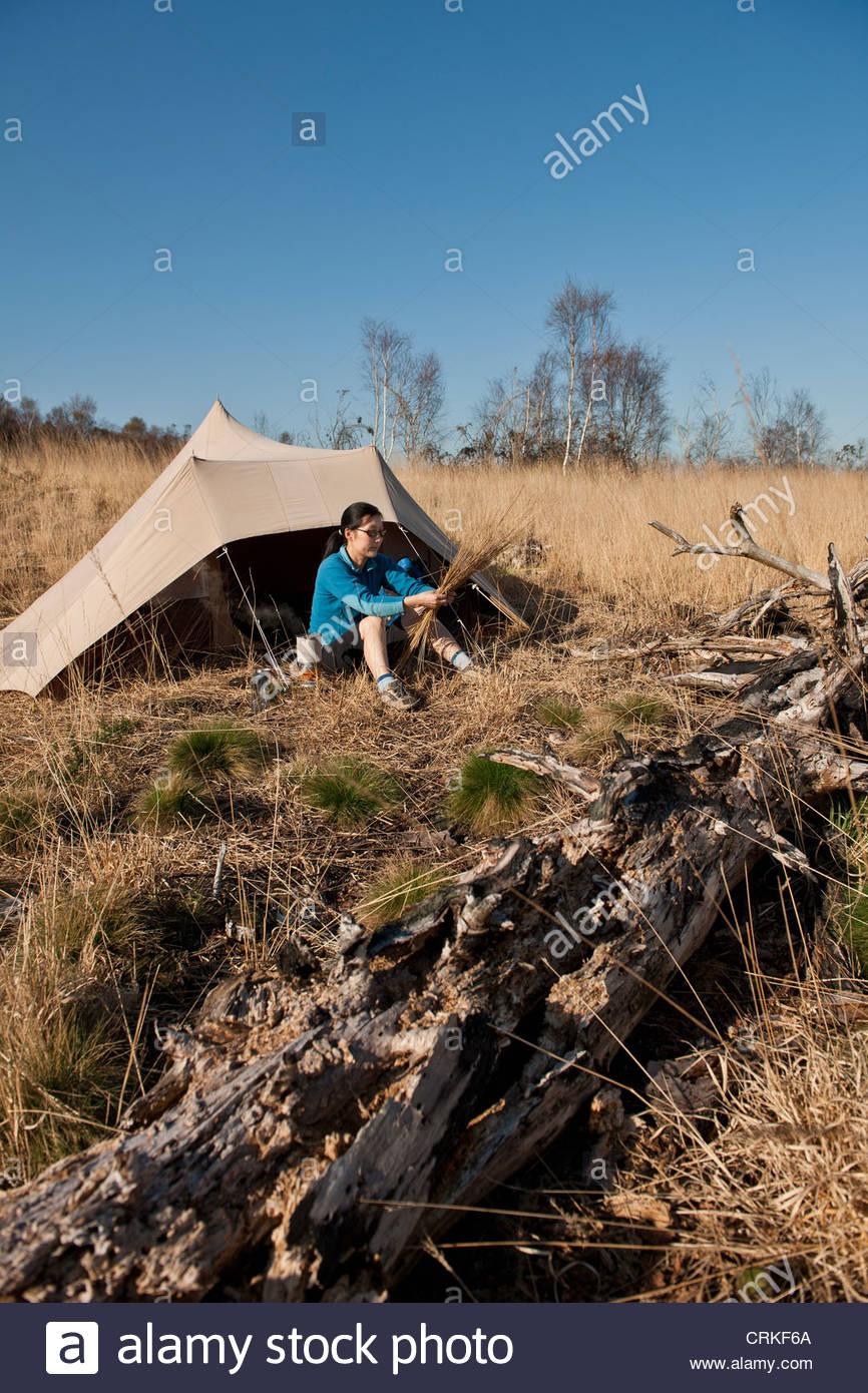 Caminante sentado por camp carpa en hierba alta Imagen De Stock