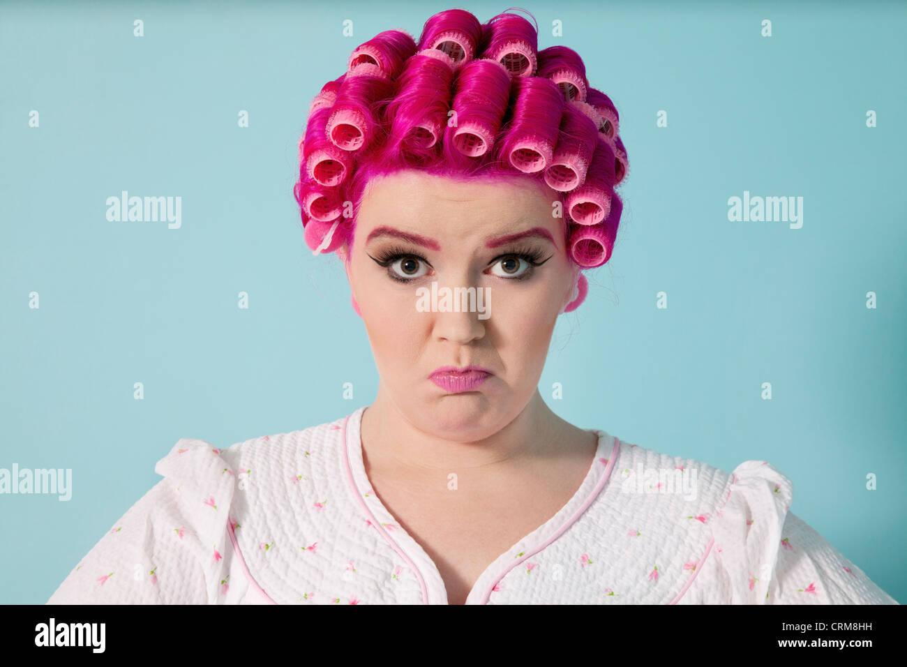 Retrato de mujer joven gesticulaciones con rizadores de pelo sobre fondo de color Imagen De Stock