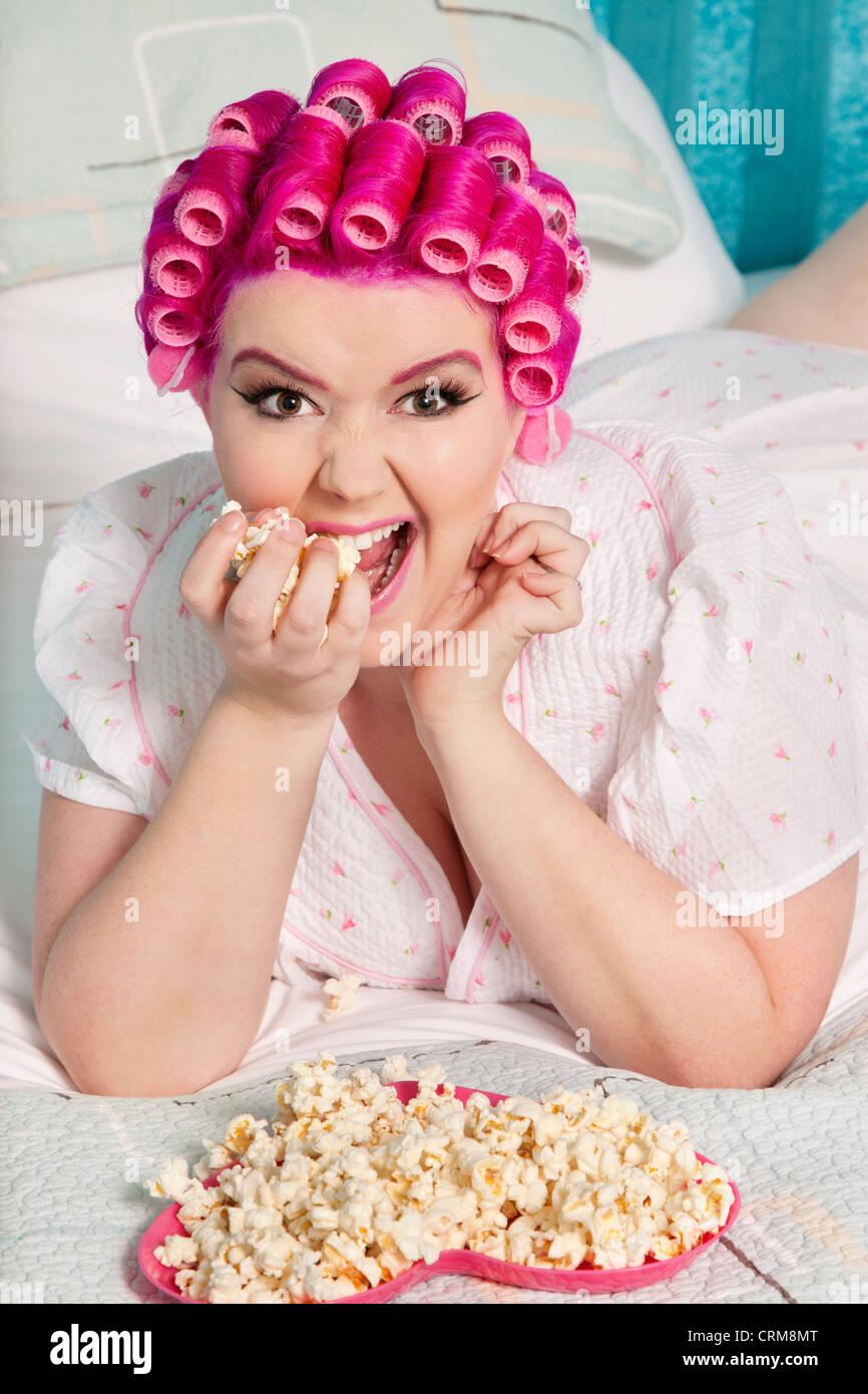 Retrato de mujer joven con rulo comiendo palomitas Imagen De Stock