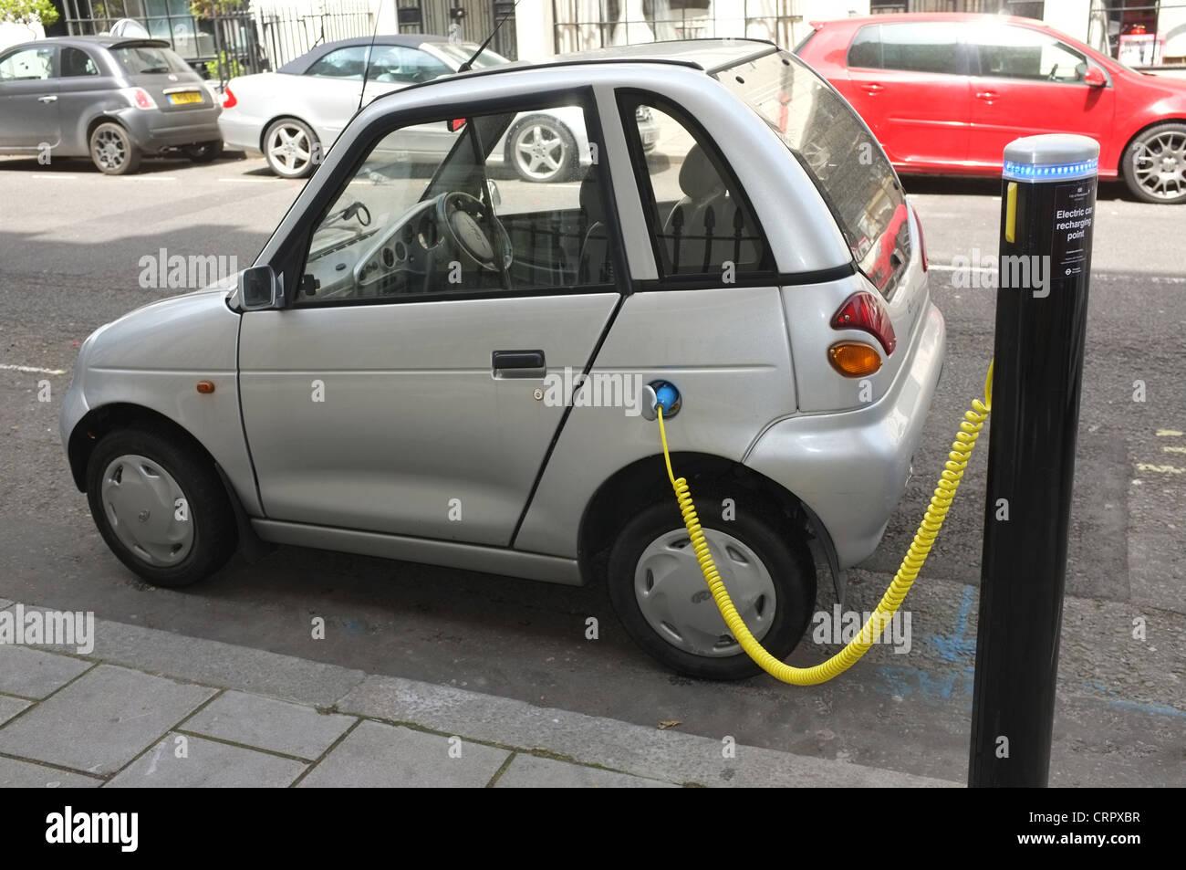 Un G-Wiz coche eléctrico conectado a un punto de recarga en la calle Hinde Westminster Imagen De Stock