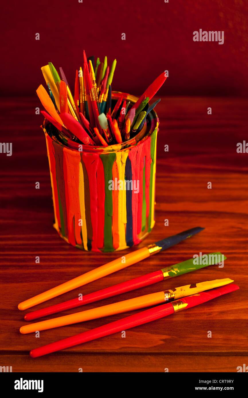 Brochas de pintura multicolor en una lata de pintura cubierto con pintura gotea Imagen De Stock