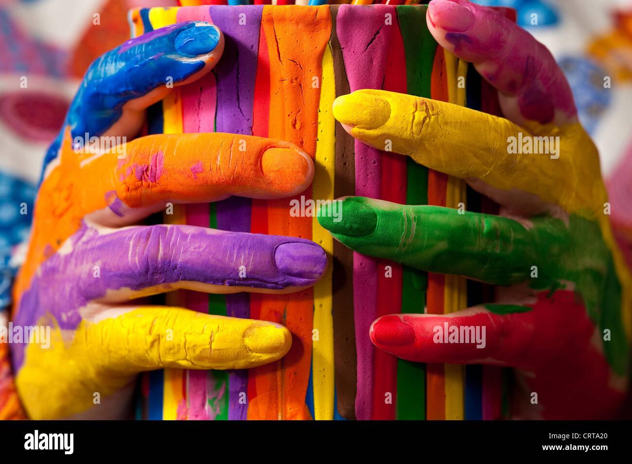 Close-up de mujer sosteniendo la pintura multicolor con dedos pintados Foto de stock