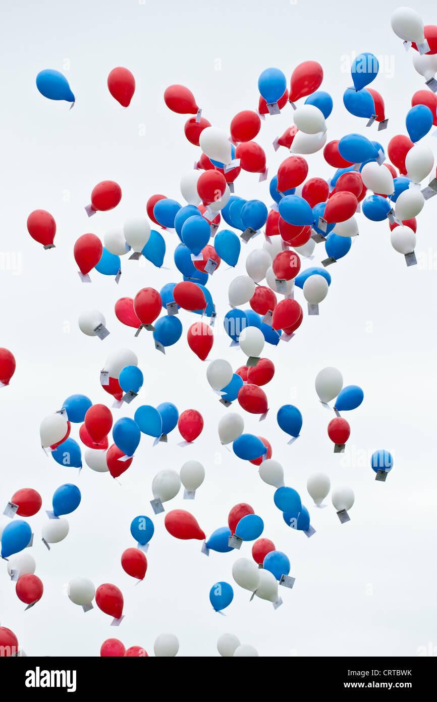 Rojo, globos de colores blanco y azul contra un cielo blanco Imagen De Stock