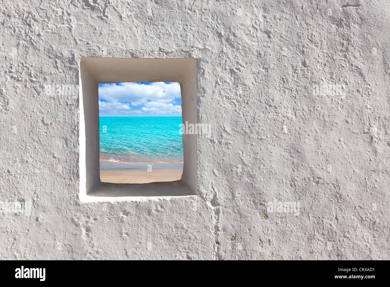 Islas Baleares idílica playa turquesa vista a través de casas encaladas puerta abierta Imagen De Stock