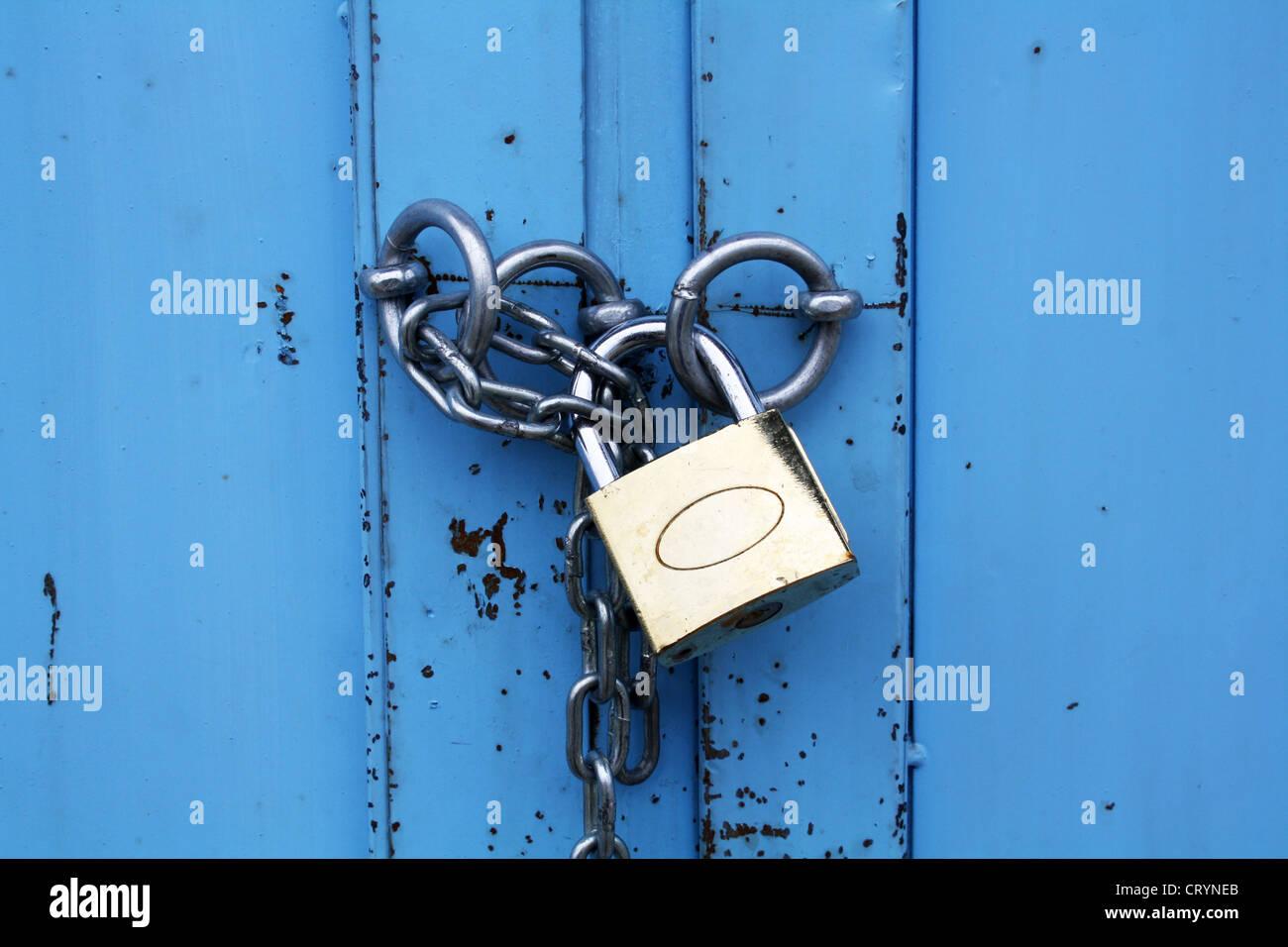 Candado con cadena en la puerta de metal azul Foto de stock