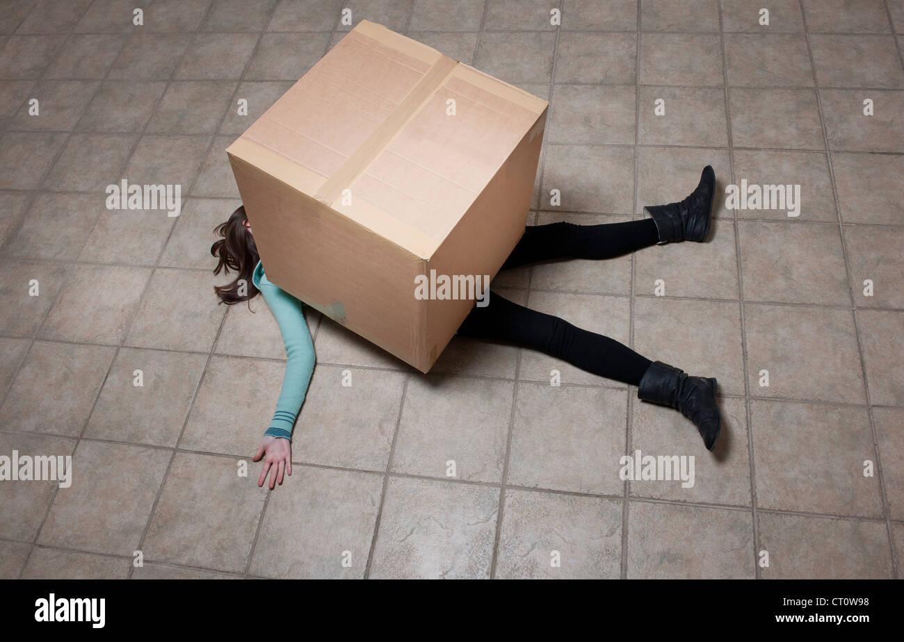 Adolescente que yacía bajo la caja de cartón Foto de stock