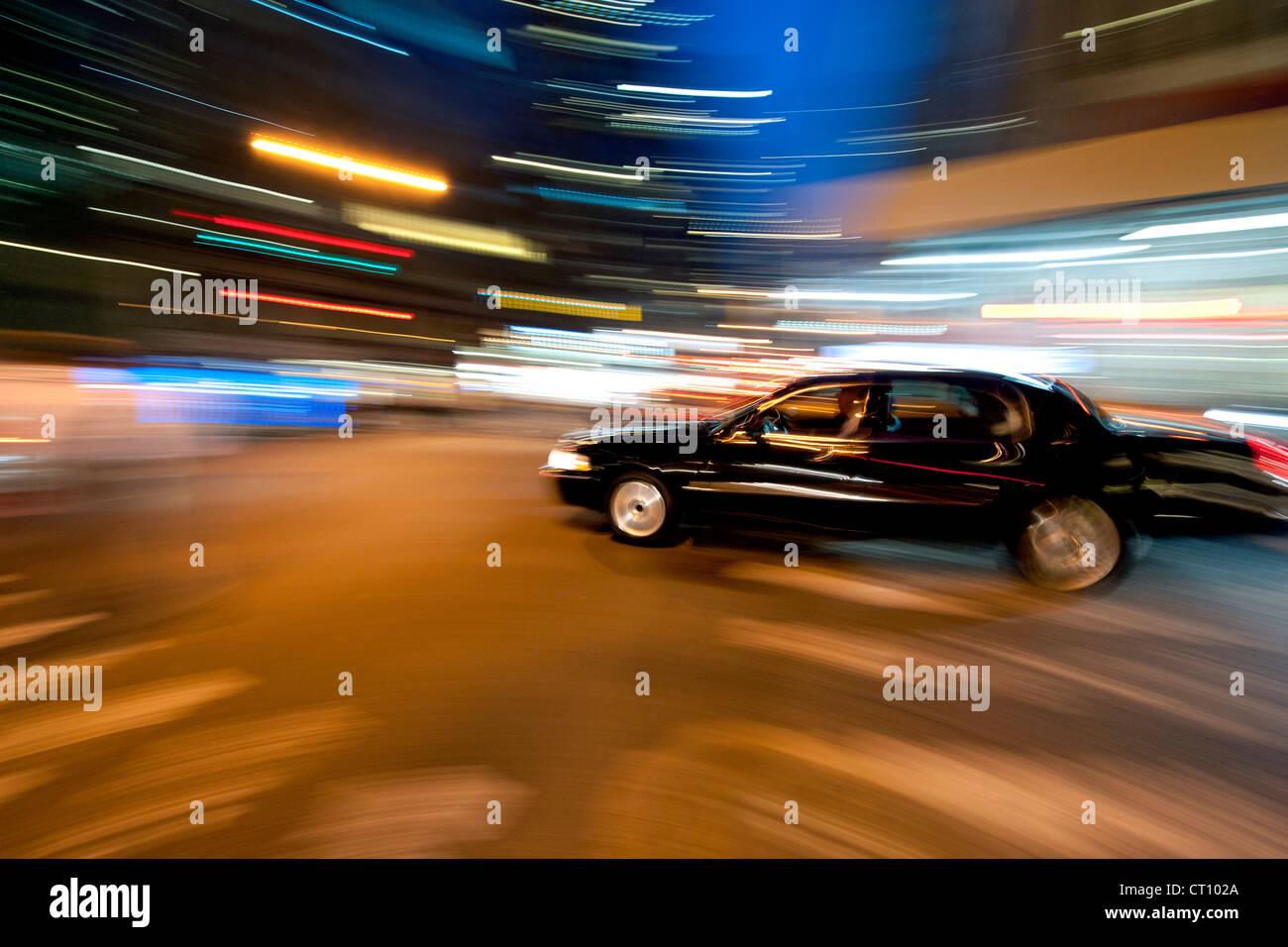 Movimiento-imagen borrosa de un sedán negro conduciendo a través de Manhattan en Nueva York en la noche. Imagen De Stock