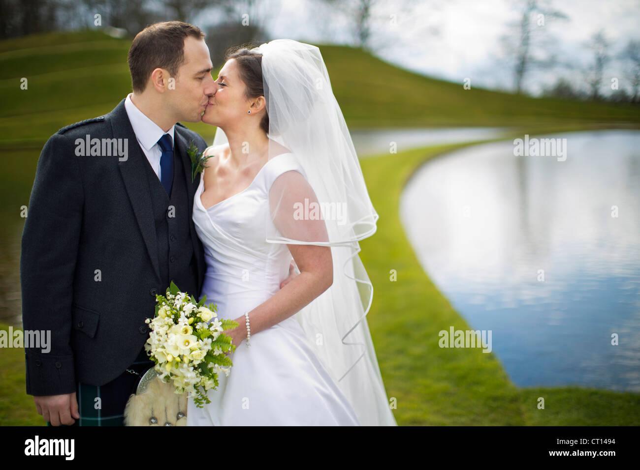 Pareja de recién casados besos al aire libre Imagen De Stock