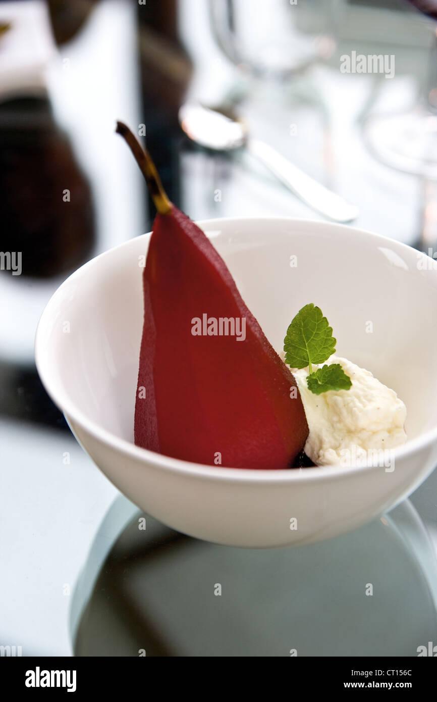 Tazón de pera cocida y crema Imagen De Stock