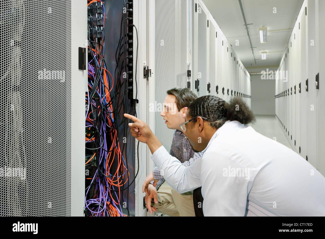 Los empresarios examinar los cables en el servidor Foto de stock