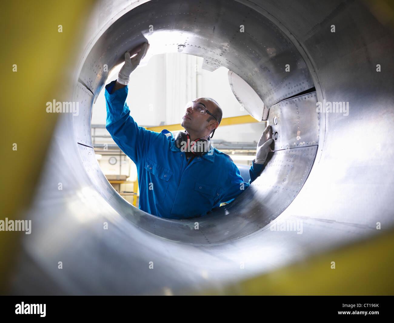 Los trabajadores examinar la maquinaria de avión Imagen De Stock