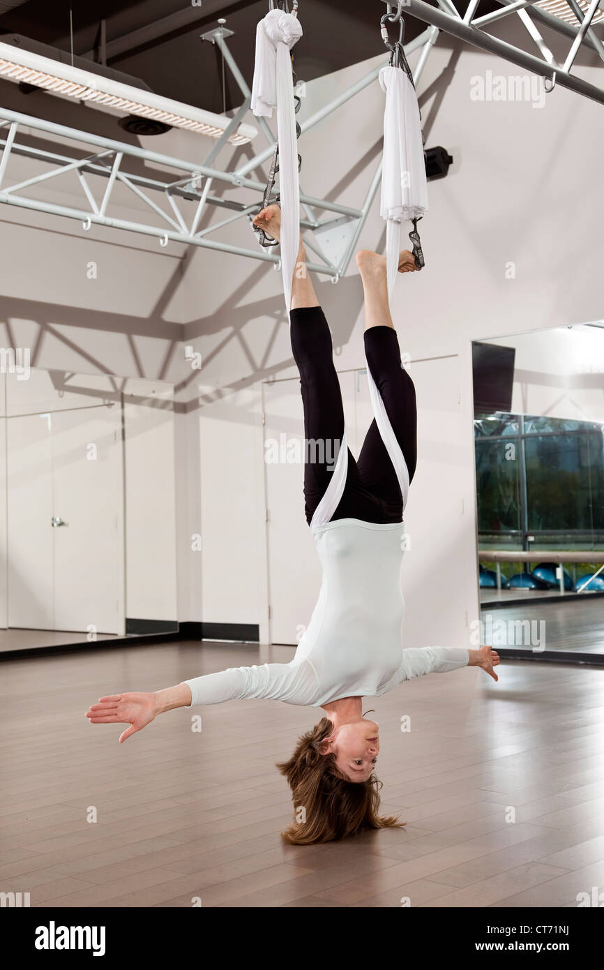 Mujer yoga antigravedad haciendo ejercicio en el gimnasio. Imagen De Stock