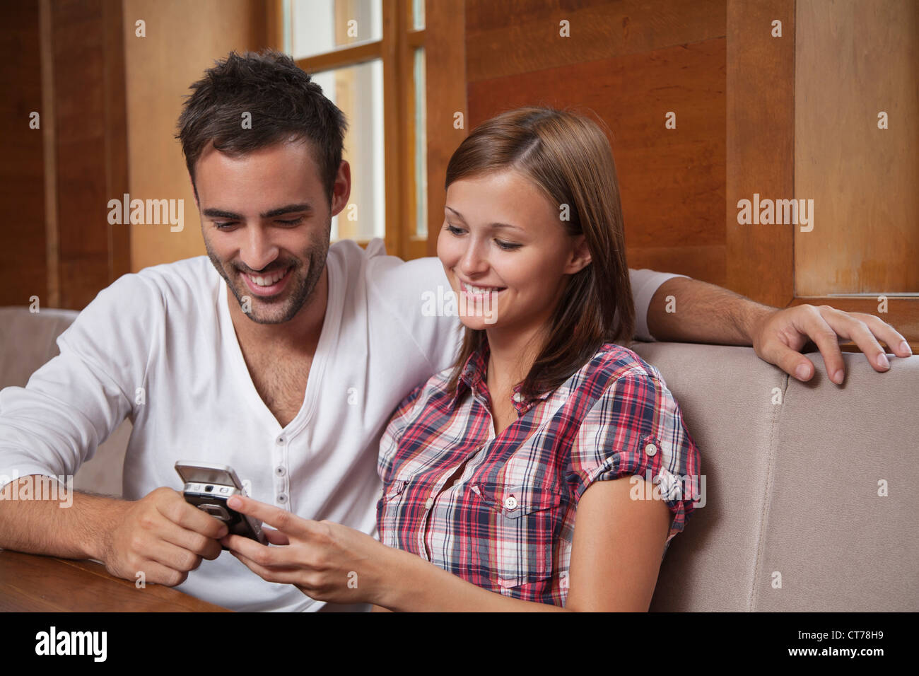 Pareja joven compartir mensaje de texto por teléfono móvil Imagen De Stock