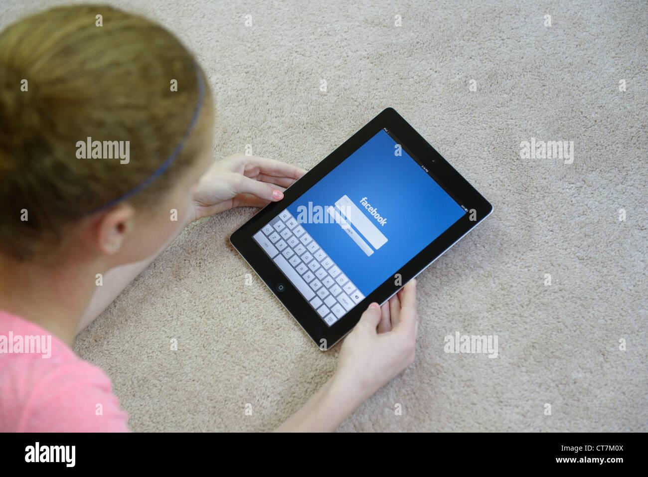 Chica busca en el iPAD con el teclado para acceder a Facebook Imagen De Stock