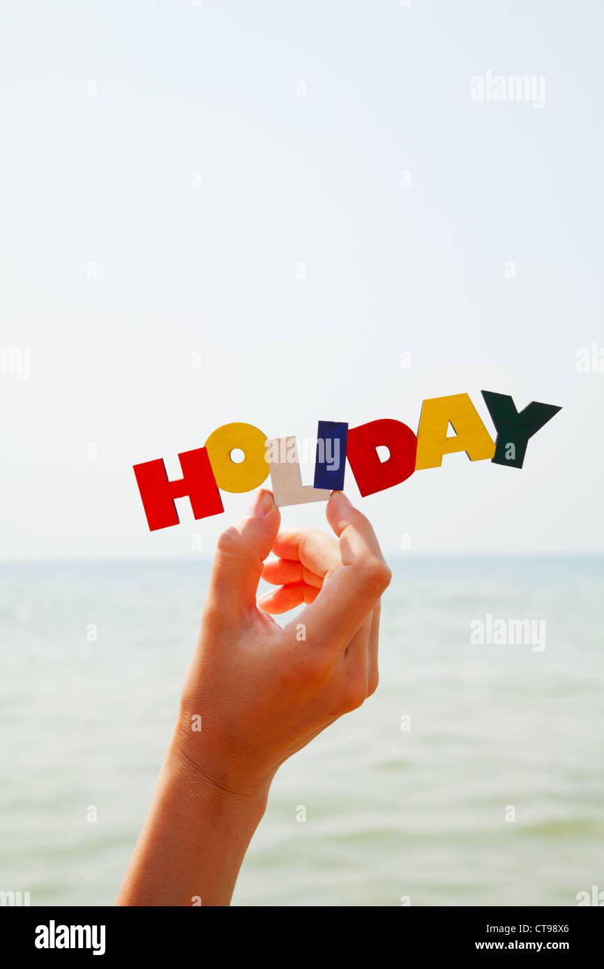 La mano femenina sosteniendo coloridos palabra 'Vacaciones' contra el mar a la luz del día Imagen De Stock