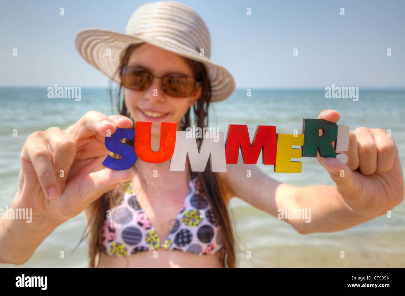 Jovencita en una playa con la palabra 'veraniego'! Imagen De Stock