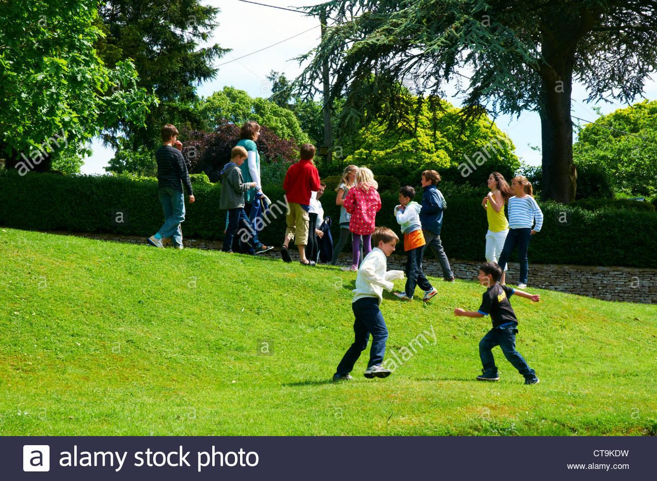 Un Grupo De Ninos Jugando Juegos Al Aire Libre En Un Pueblo Verde