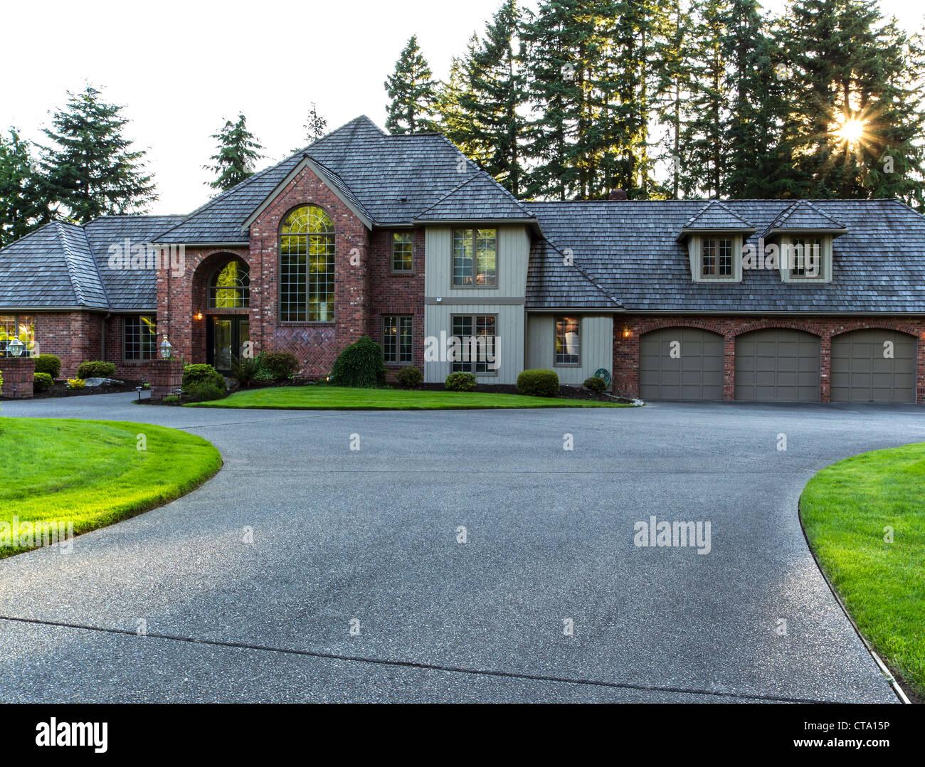 Entrada a gran casa de ladrillo y madera de cedro con árboles y sol en segundo plano. Imagen De Stock