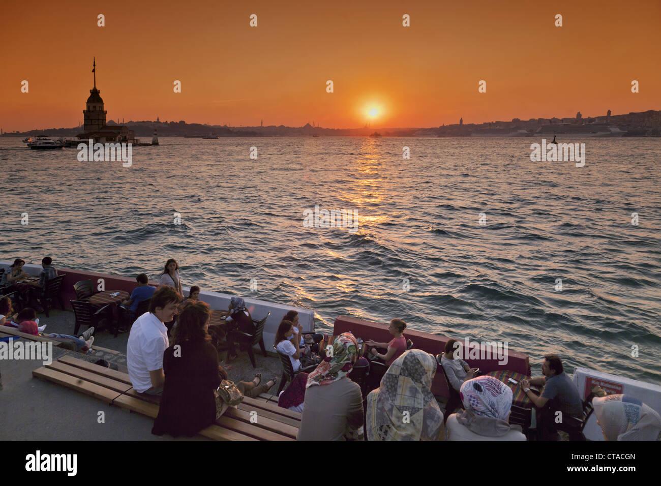 Lounge en el Bosporus Waterfront, Kis Kulesi torre al atardecer, Estambul, Turquía, Europa Imagen De Stock