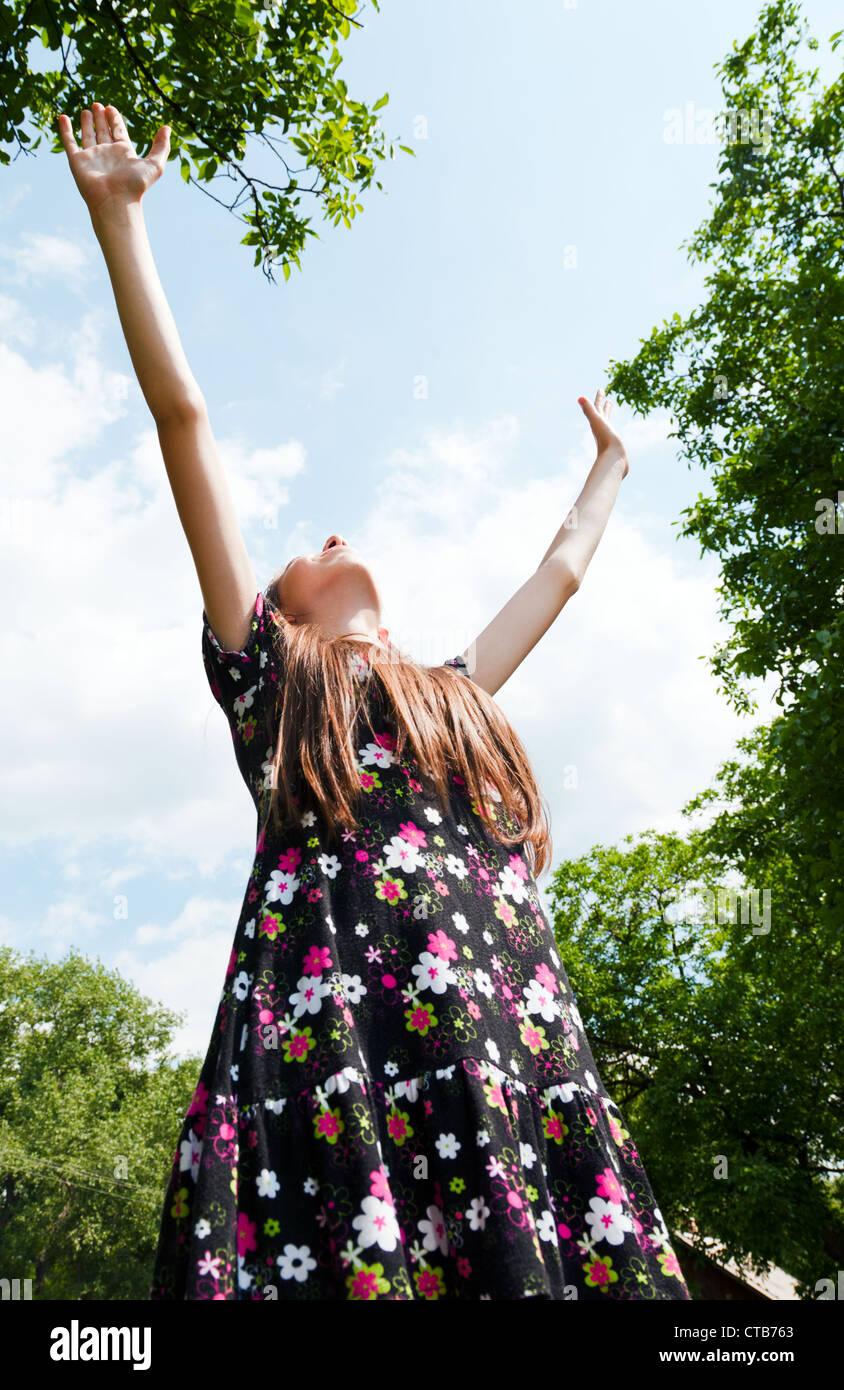 Jovencita con manos levantadas contra el azul cielo nublado Imagen De Stock