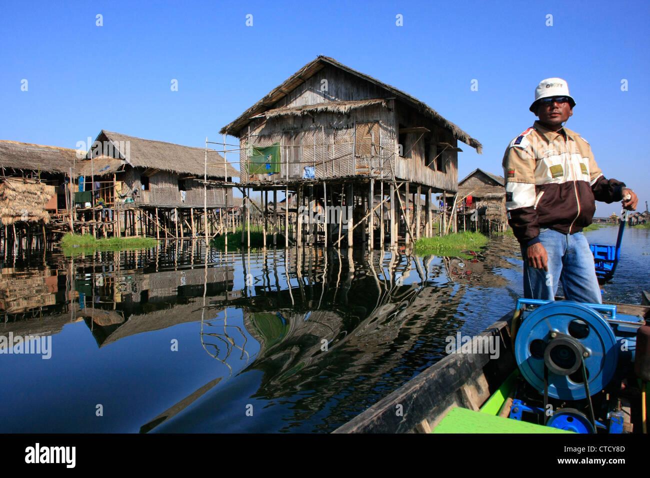 Barquero birmano conduciendo a través de pueblo flotante del lago Inle, el estado de Shan, en Myanmar, en el sudeste de Asia Foto de stock
