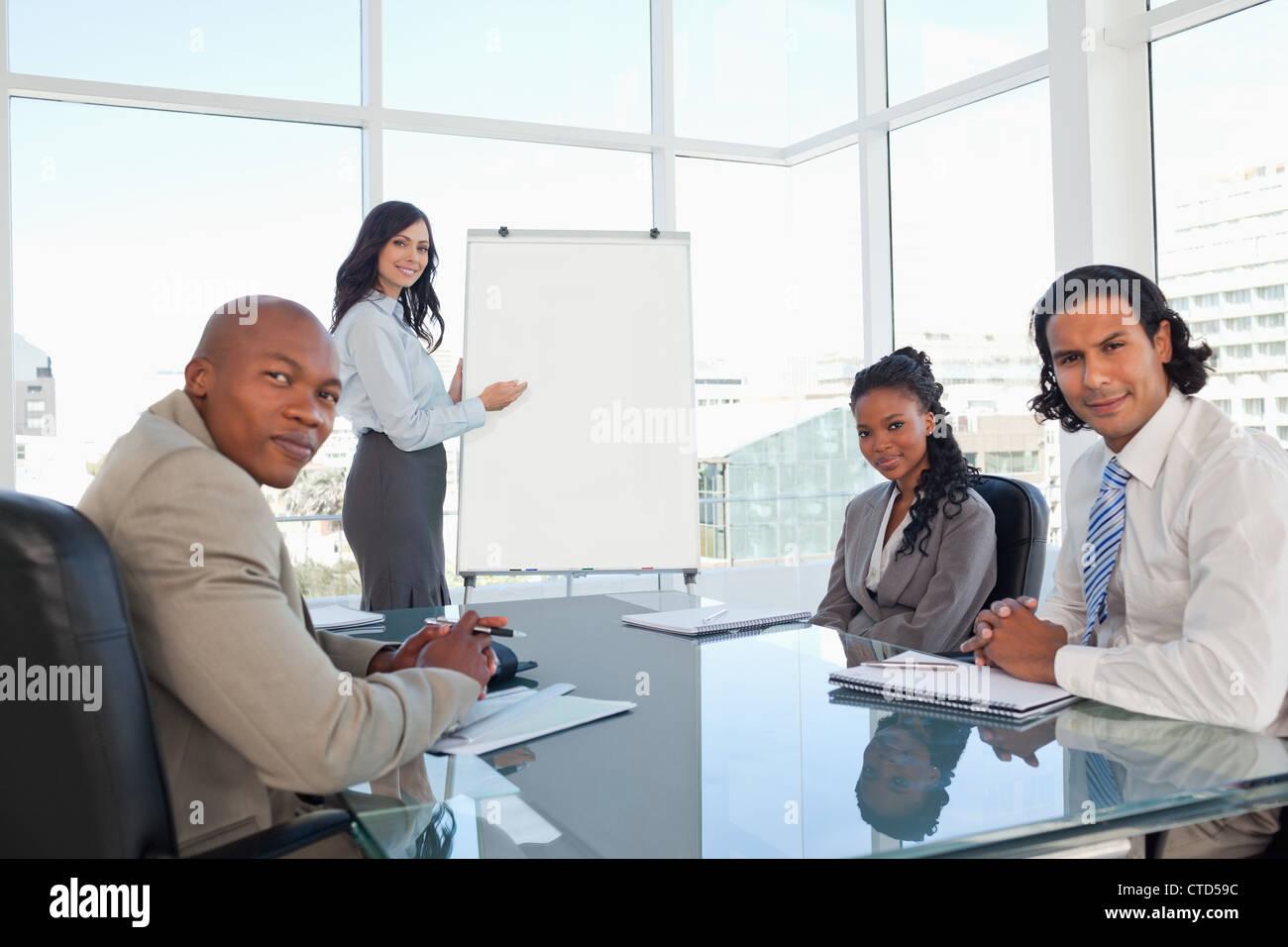Equipo empresarial casi sonriente en una sala durante una presentación Foto de stock