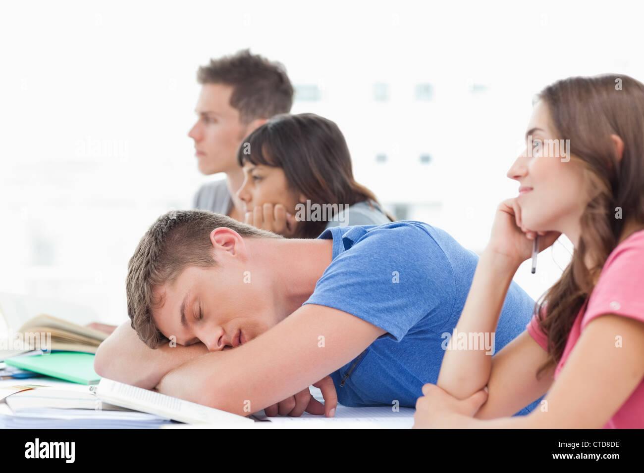 Cuatro estudiantes en clase como tres preste atención un estudiante varón duerme Foto de stock
