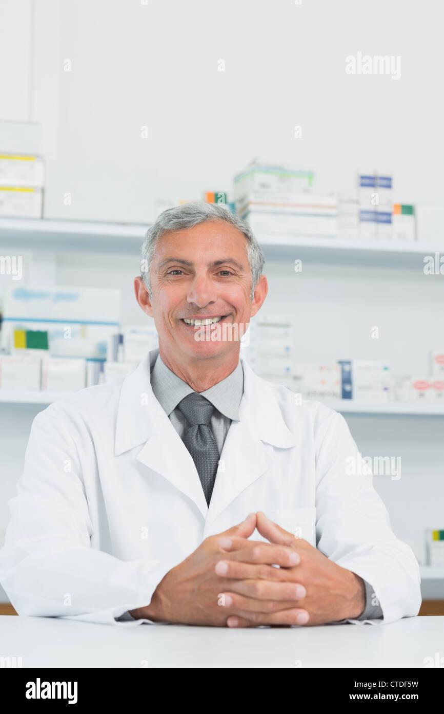 Macho sonriente farmacéutico con sus manos se unió en un contador Imagen De Stock