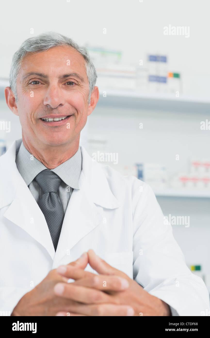 Sonriendo farmacéutico con sus manos se unió en el mostrador de una farmacia Imagen De Stock