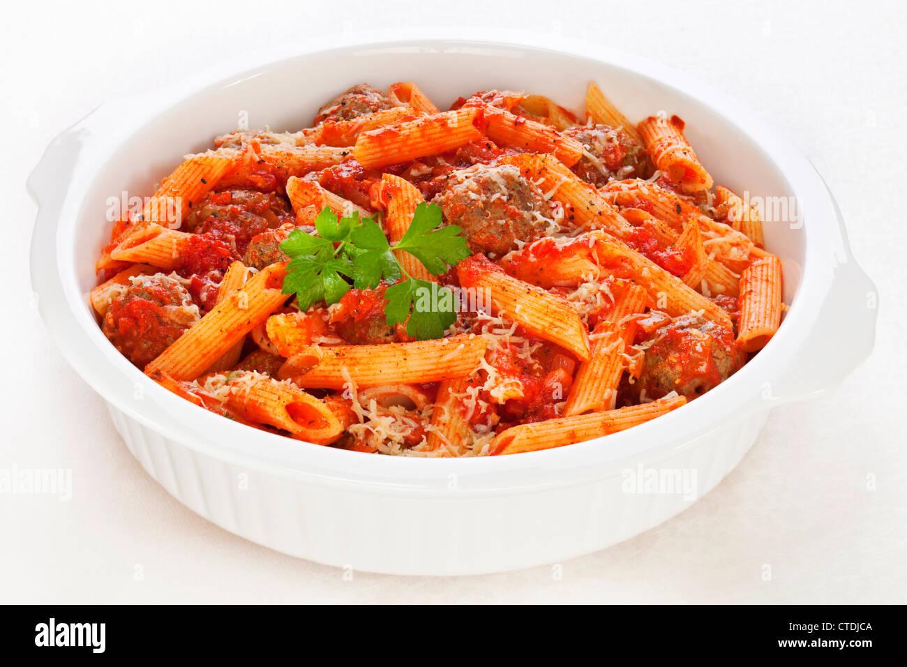 Albóndigas en salsa de tomate con pasta penne y queso parmesano al horno. Imagen De Stock