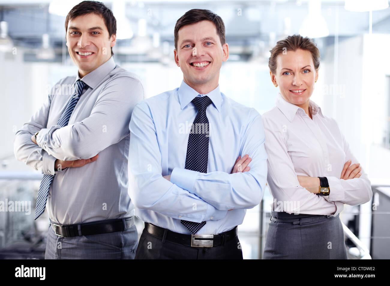 Elegante equipo empresarial permanente armado cruzada expresando positividad y fuerte influencia Imagen De Stock
