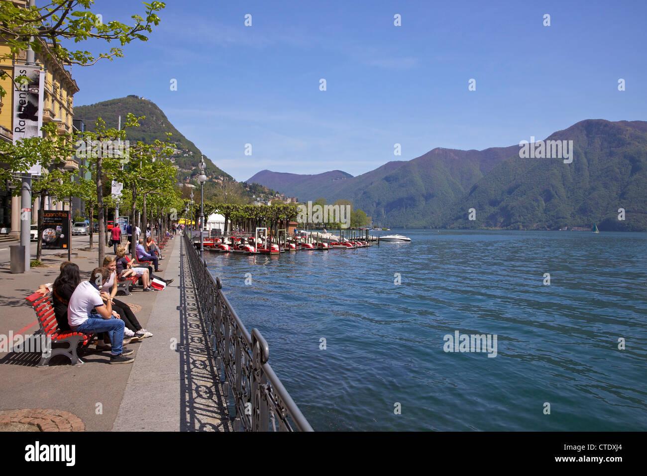 Los visitantes disfrutando del sol junto al lago, la ciudad de Lugano, el lago de Lugano, Ticino, Suiza, Europa Imagen De Stock
