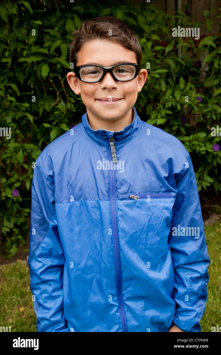 Chico en un anorak azul sonriendo ante la cámara. Imagen De Stock