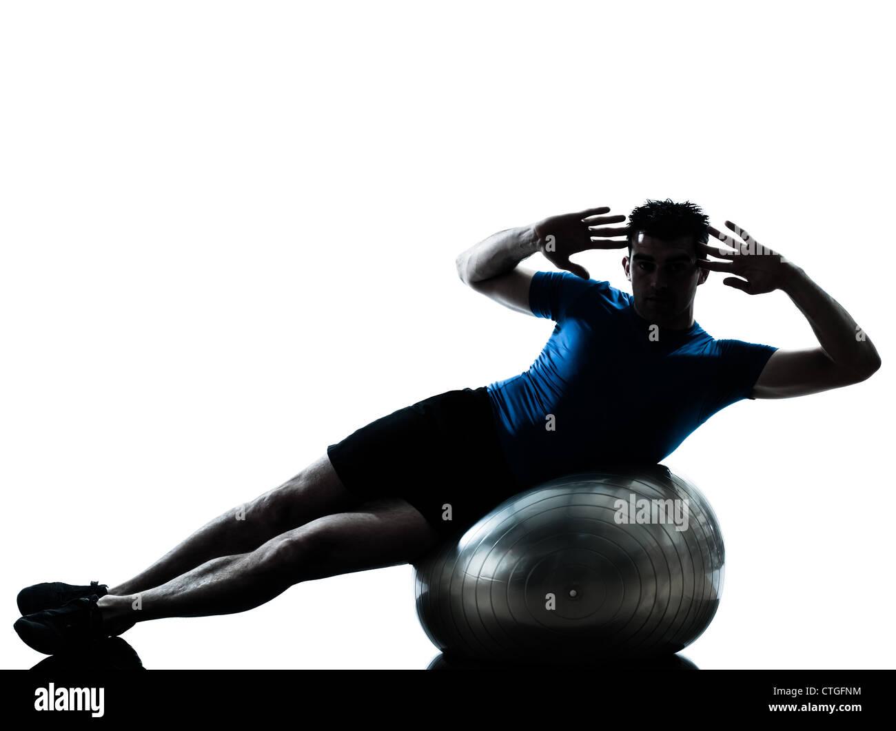 Un hombre caucásico ejercicio workout fitness ball en silueta studio aislado  sobre fondo blanco. Imagen 6ffc6eea84b2