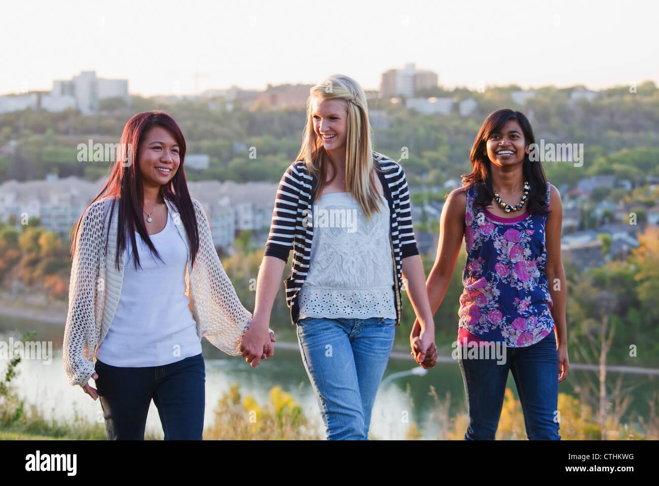 Amigos caminando en un parque de la ciudad con el perfil de la ciudad de fondo; en Edmonton, Alberta, Canadá Foto de stock
