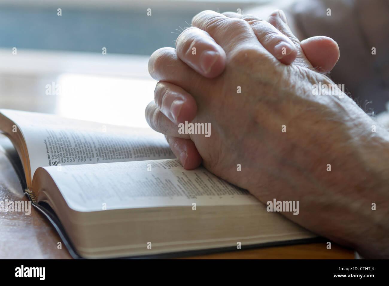 Old Man's ensuciándose las manos entrelazadas en la oración a través de Biblia abierta Imagen De Stock