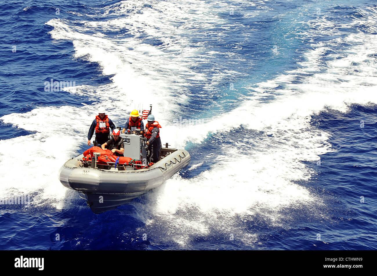 Los marineros asignados al destructor de misiles guiados de la clase Arleigh Burke USS McCampbell (DDG 85) regresan al barco después de rescatar a una víctima simulada en el agua durante un simulacro de hombre al mar. McCampbell está desplegado hacia adelante en Yokosuka, Japón, y está en marcha en el área de responsabilidad de la 7a flota de los Estados Unidos. Foto de stock