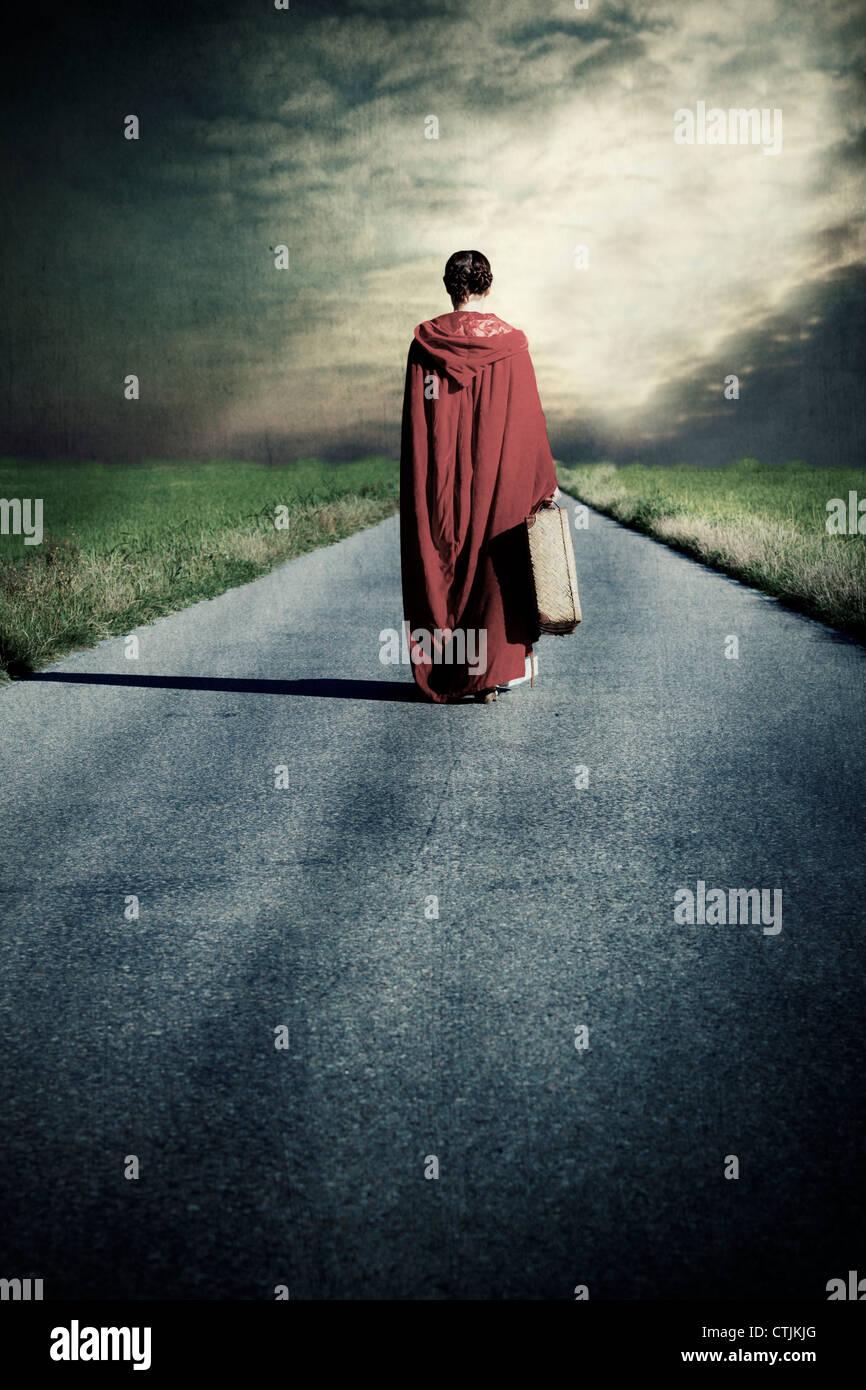 Una mujer en un capote rojo está andando por un camino con una maleta Imagen De Stock