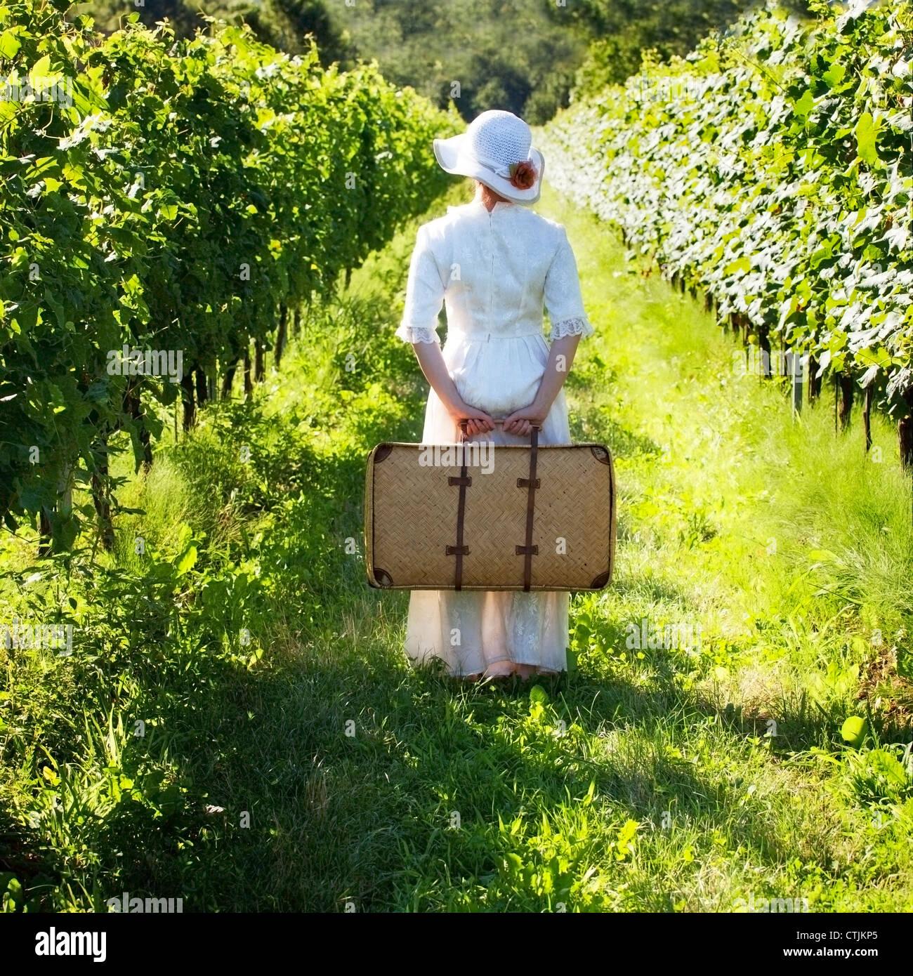 Una mujer en un vestido blanco de estilo victoriano, está caminando a través de los viñedos Foto de stock