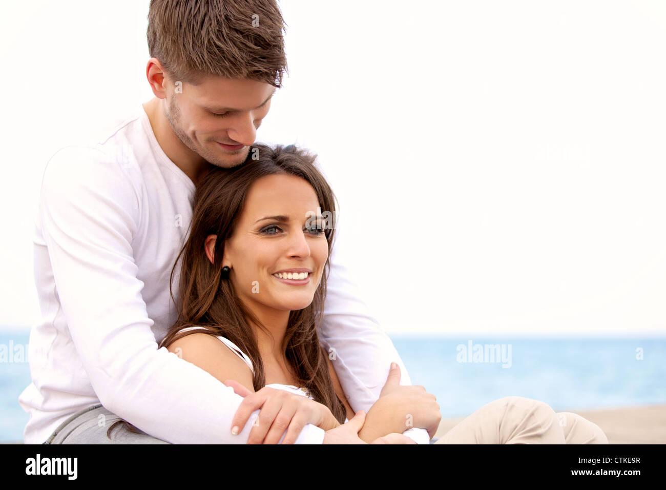 Retrato de una pareja atractiva colgando por el mar contra un fondo brillante Foto de stock